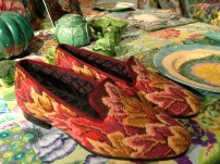 Only Kaffe can make needlepoint slippers look good on dining table.